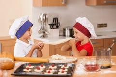 Kleine Kinder, die Bäckerei und das Spielen machen Stockfoto