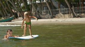 Kleine Kinder, die das Meer surfboarding und gesprungen worden sein würden in Wasser in der Zeitlupe genießen stock footage