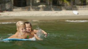 Kleine Kinder, die das Meer surfboarding und gesprungen worden sein würden in Wasser in der Zeitlupe genießen stock video