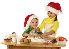 Kleine Kinder, die den Weihnachtskuchen kochen Stockbilder