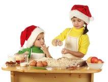 Kleine Kinder, die den Weihnachtskuchen kochen Stockfoto