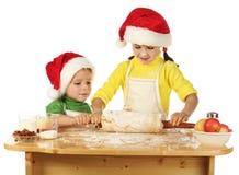 Kleine Kinder, die den Weihnachtskuchen kochen Stockbild