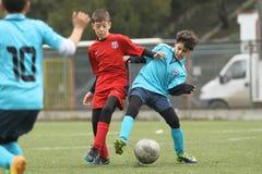Kleine Kinder, die Fußball oder Fußball spielen Stockbilder