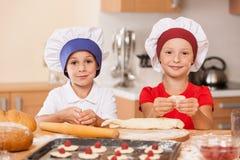 Kleine Kinder, die Kuchen und das Lächeln machen Stockfotografie