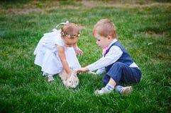 Kleine Kinder, die mit einem Kaninchen im Park spielen Stockfoto