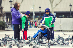 Kleine Kinder, die mit Tauben spielen Kinder in Barcelona, Spanien Stockbild