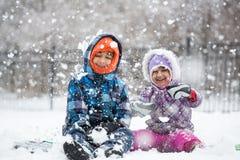 Kleine Kinder, die Schneefälle genießen Stockfotos