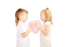 Kleine Kinder, Junge und Mädchen, die Herz halten Stockbild