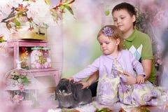 Kleine Kinder mit Kaninchen Stockfoto