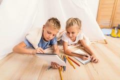 Kleine Kinder vernarrt in zu Hause malen stockfotos