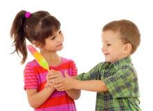 Kleine Kinder, welche die FarbenEiscreme teilen stockfotos