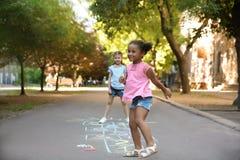 Kleine Kinder, welche die Hopse gezeichnet mit bunter Kreide spielen lizenzfreies stockbild