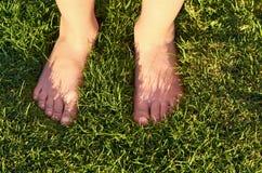 Kleine Kinderbeine legt auf grünes Gras lizenzfreie stockfotos