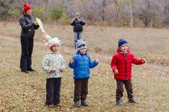 Kleine kinderen in de herfstjasjes en ouders die in de herfstbos spelen stock foto