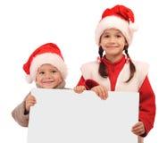 Kleine kinderen in de hoeden van Kerstmis met banner Stock Foto's