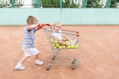 Kleine kinderen die bij een tennisbaan met het winkelen karretje spelen stock fotografie