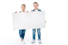 Kleine kinderen die lege banner houden en bij camera glimlachen stock fotografie