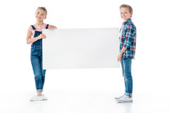 Kleine kinderen die lege banner houden en bij camera glimlachen stock afbeelding