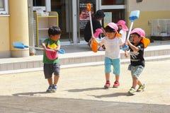 Kleine kinderen die lepels spelen in openlucht, Takayama, Japan stock foto