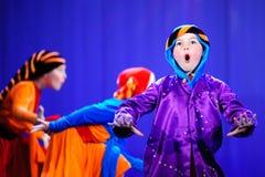 Kleine kinderen die met oude oosterse kostuums op stadium dansen stock foto's