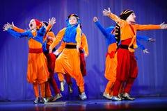 Kleine kinderen die met oude oosterse kostuums op stadium dansen royalty-vrije stock fotografie