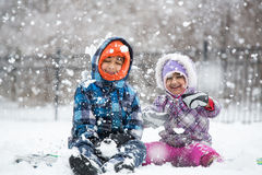 Kleine Kinderen die van Sneeuwval genieten Stock Foto's