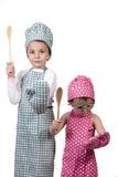 Kleine kinderen, met een houten lepel en kokkostuum Stock Foto