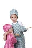 Kleine kinderen, met een houten lepel en kokkostuum Stock Fotografie