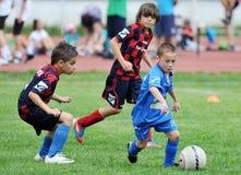 Kleine Kinderjungenspielfußball oder -fußball Stockbilder