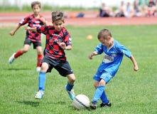 Kleine Kinderjungenspielfußball oder -fußball Stockfotografie