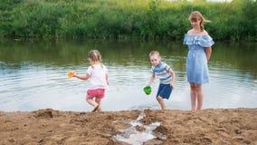 Kleine Kinderspiel im Fluss im Sommer, ein Mädchen und ein Junge errichten einen Strom Mutter kümmert sich um Babys während a stock footage