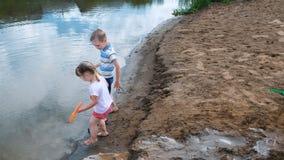 Kleine Kinderspiel im Sand auf dem Fluss Kinder errichten einen Nebenfluss mit Eimern und einer Schaufel stock video