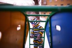 Kleine kindspelen bij speelplaats in de winter Stock Fotografie