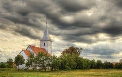 Kleine Kirche gegen drastischen Himmel Lizenzfreies Stockfoto