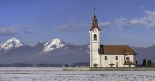 Kleine Kirche mit alpinem Hintergrund, Slowenien Lizenzfreie Stockfotos