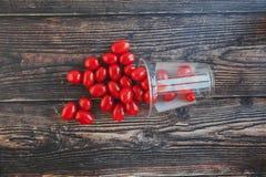 Kleine Kirschtomaten in einem Glas auf einem schwarzen Holztisch stockfoto