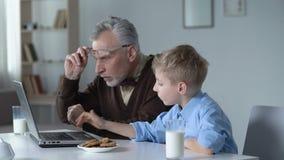 Kleine kleinzoon die grootvader tonen hoe te om laptop te gebruiken, gemakkelijk om software te leren stock video