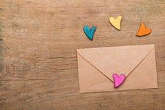 Kleine kleurrijke harten en envelop op houten achtergrond Royalty-vrije Stock Afbeeldingen