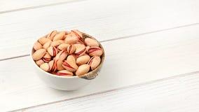 Kleine kom met pistaches op wit raadsbureau, ruimte voor tekst op rechterkant royalty-vrije stock fotografie