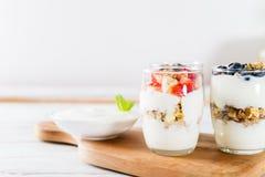 Kleine Kruiken met gelaagd dessert van natuurlijke yoghurt, granola royalty-vrije stock afbeelding