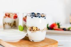 Kleine Kruiken met gelaagd dessert van natuurlijke yoghurt, granola royalty-vrije stock foto's