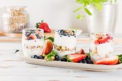 Kleine Kruiken met gelaagd dessert van natuurlijke yoghurt, granola royalty-vrije stock fotografie