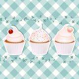 Kleine Kuchen auf blauem Gingham lizenzfreie abbildung