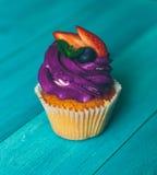Kleine Kuchen auf einem hölzernen Hintergrund der blauen Weinlese Stockfoto