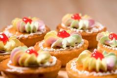 Kleine Kuchen auf hölzerner Tabelle Lizenzfreies Stockfoto