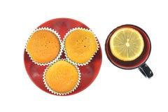 Kleine Kuchen auf Platte mit einer Tasse Tee Lizenzfreie Stockfotos