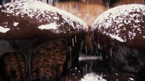 Kleine Kuchen der Zeitlupe zwei in der Glasur besprühen mit Puderzuckerabschluß oben stock video footage