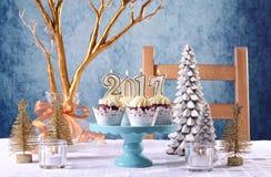 Kleine Kuchen des neuen Jahres 2017 auf einem Winterthemagedeck Stockfotografie
