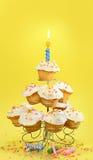 Kleine Kuchen mit blauer Kerze auf Gelb Lizenzfreies Stockbild
