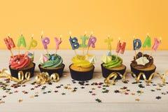 Kleine Kuchen mit den Kerzen alles Gute zum Geburtstag des Wortes buchstabierend Stockbilder